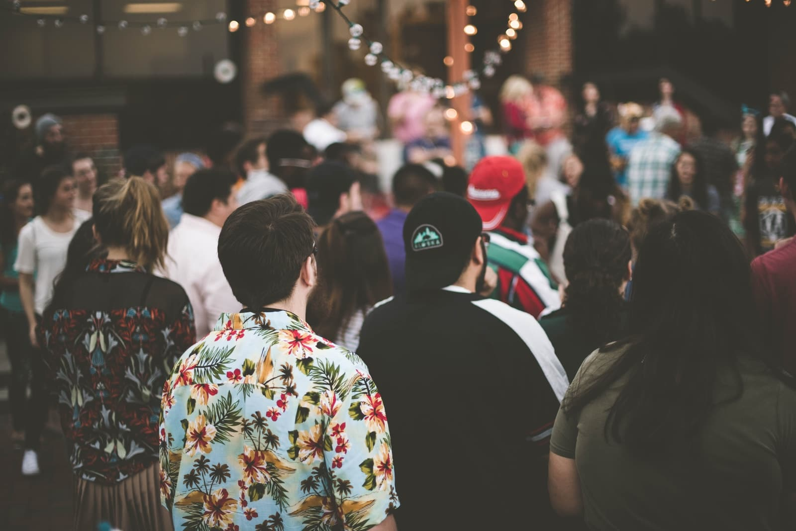 group of people standing under string lights